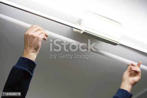istock Electrician man worker installing fluorescent lamp 1134506378