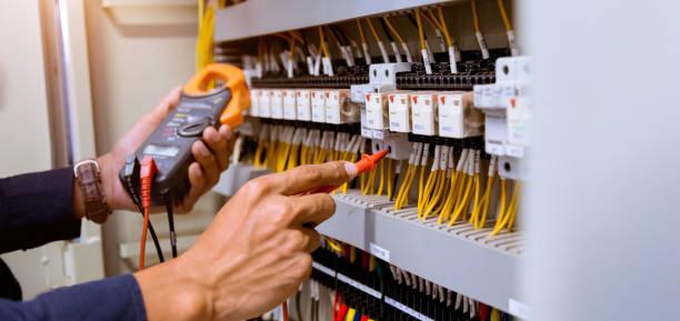 elektricien metingen met multimeter testen huidige elektrische in het bedieningspaneel. - elektrische fitting stockfoto's en -beelden