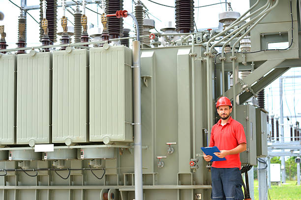 electrician near high voltage transformer - transformers stock photos and pictures