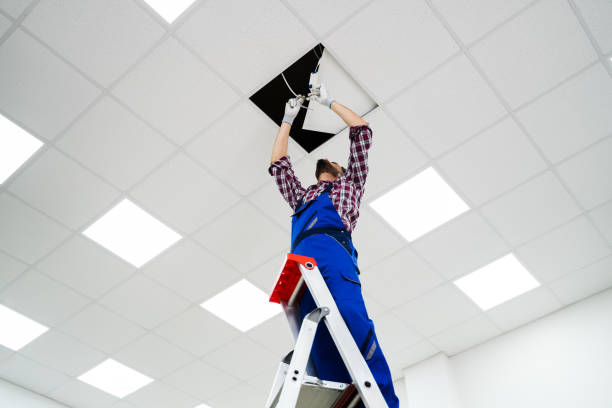electrician on stepladder installs lighting to the ceiling - led painel imagens e fotografias de stock