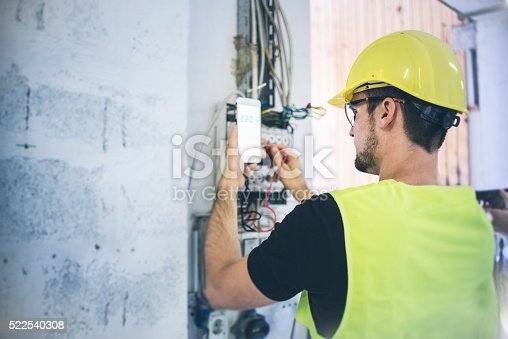 An electrician fixing up the wires and measuring volts