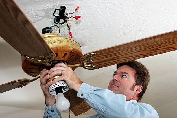 Electrician Removes Ceiling Fan An electrician removing an old ceiling fan.  The fan was installed without a ceiling box, in violation of code. Work is being performed by a licensed master electrician. ceiling fan stock pictures, royalty-free photos & images