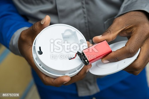 istock Electrician Removing Battery From Smoke Detector 853752026
