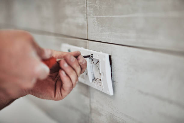 Electrician repairing / fixing wires in the wall. stock photo