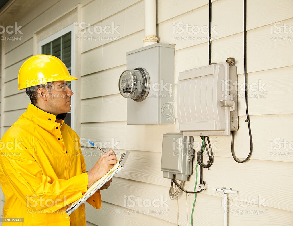 Electrician, repairman at outside electric meter on home. Yellow raincoat. stock photo
