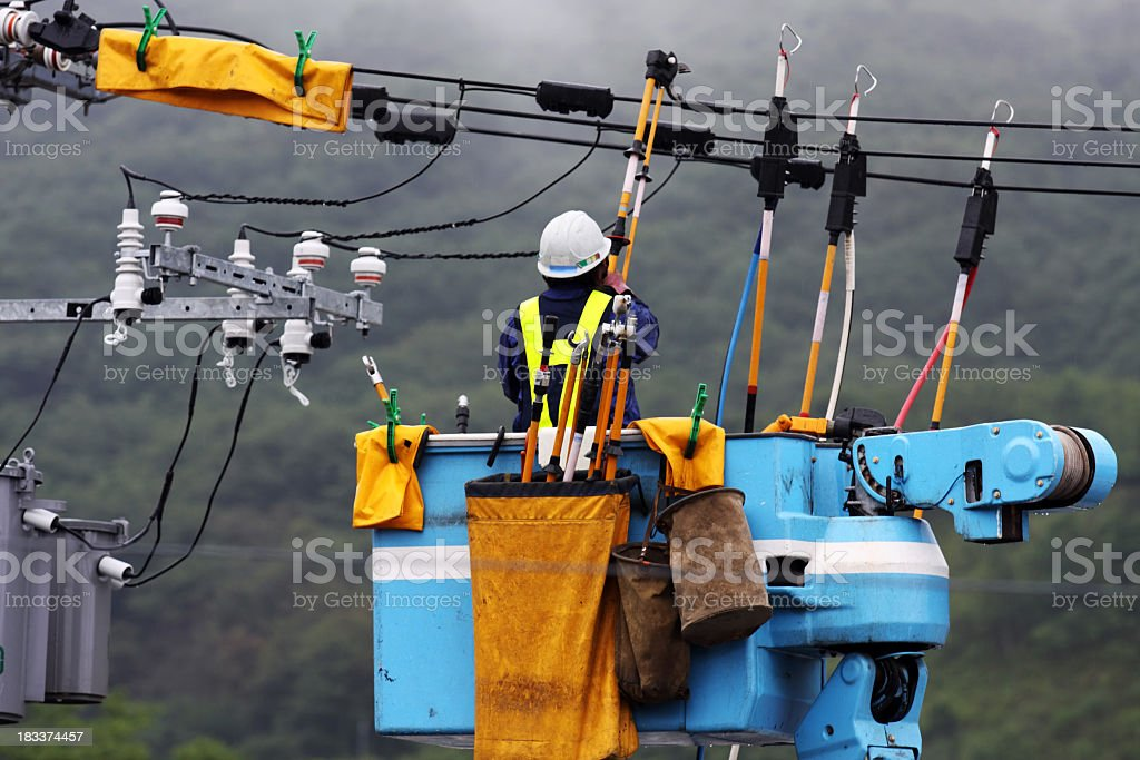 Electrician repairs a power line under the falling rain stock photo