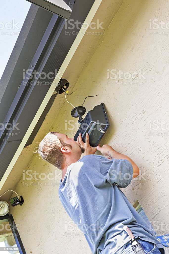 Electrician securing outdoor lighting to home royalty-free stock photo