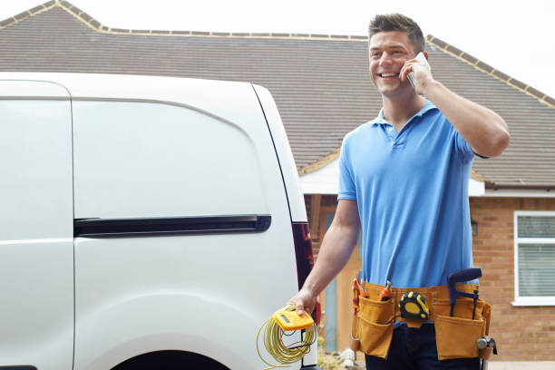 Electrician Standing Next To Van Talking On Mobile Phone Electrician Standing Next To Van Talking On Mobile Phone craftsperson stock pictures, royalty-free photos & images
