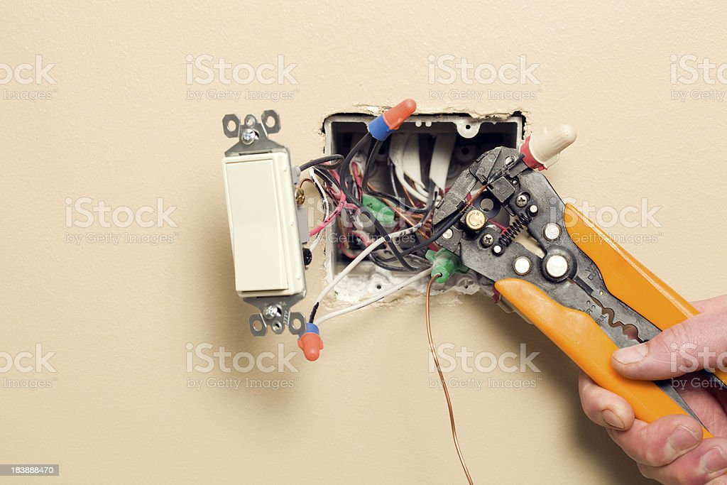 Electrician Stripping Wire for Wall Switch Box stock photo