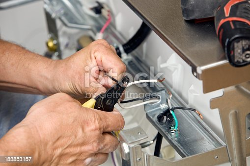 istock Electrician Strips Wires for a Dishwasher Installation 183853157