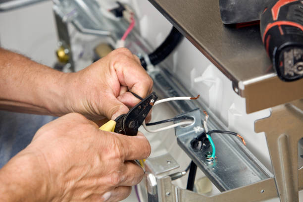 Electrician Strips Wires for a Dishwasher Installation stock photo