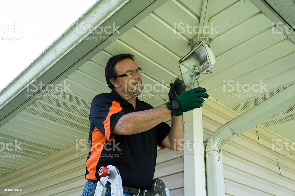 Electrician Taking Glass Cover Off Outside Light Fixture stock photo