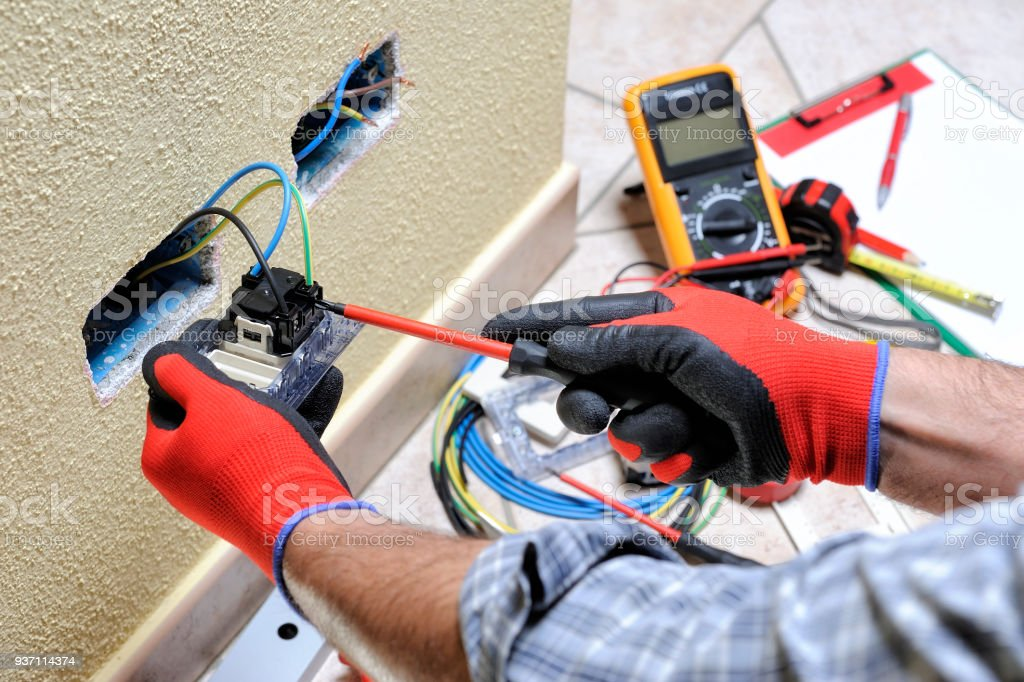 Electrician technician at work with safety equipment on a residential electrical system stock photo