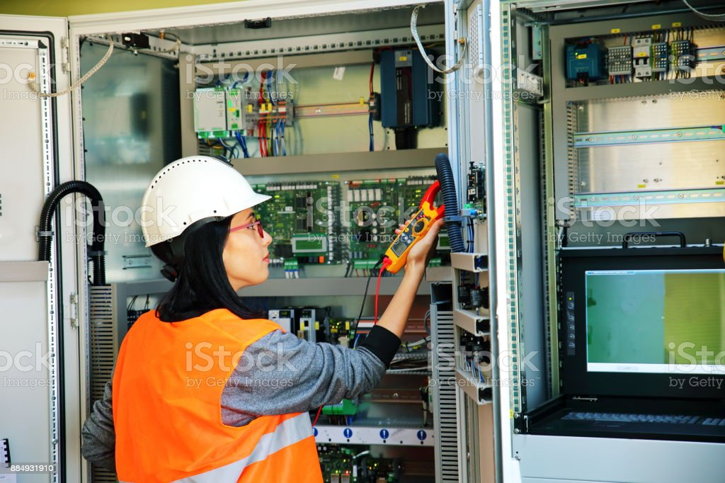 electrician testing for voltage in a fuse box - stock image