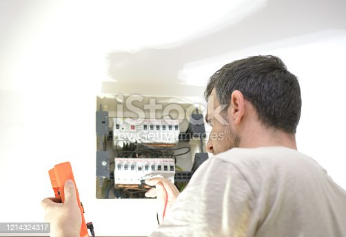 istock Electrician testing for voltage in a fuse box with instrument of measurement 1214324317