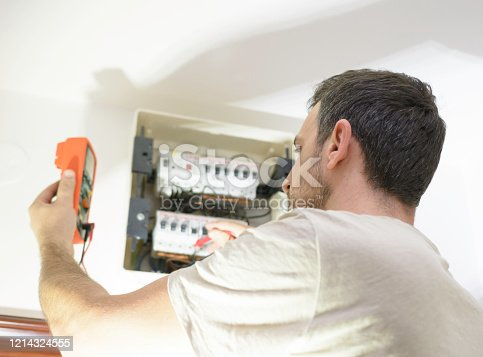 istock Electrician testing for voltage in a fuse box with instrument of measurement 1214324555
