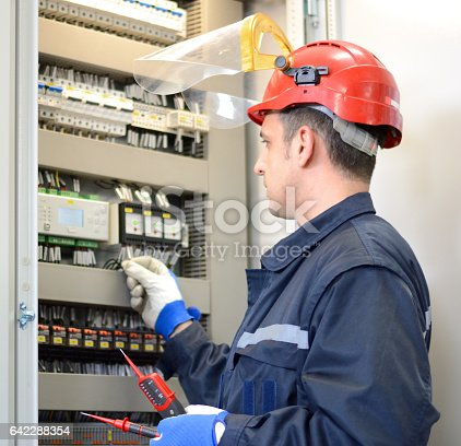 istock Electrician testing for voltage on terminal block 642288354