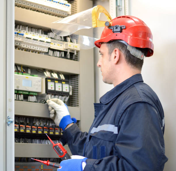 Electrician testing for voltage on terminal block stock photo
