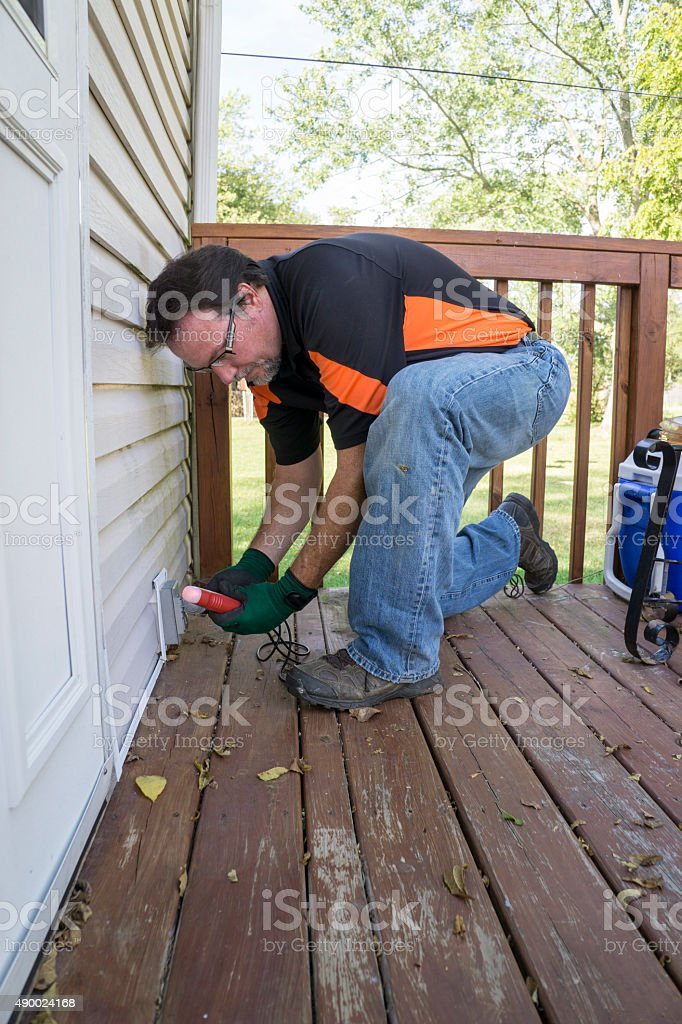 Electrician Testing Outside Outlet On Patio Deck stock photo