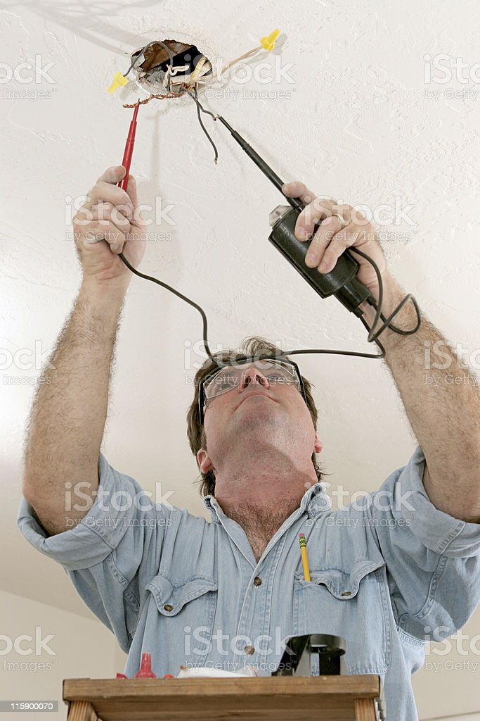 Electrician testing voltage of wires in ceiling royalty-free stock photo