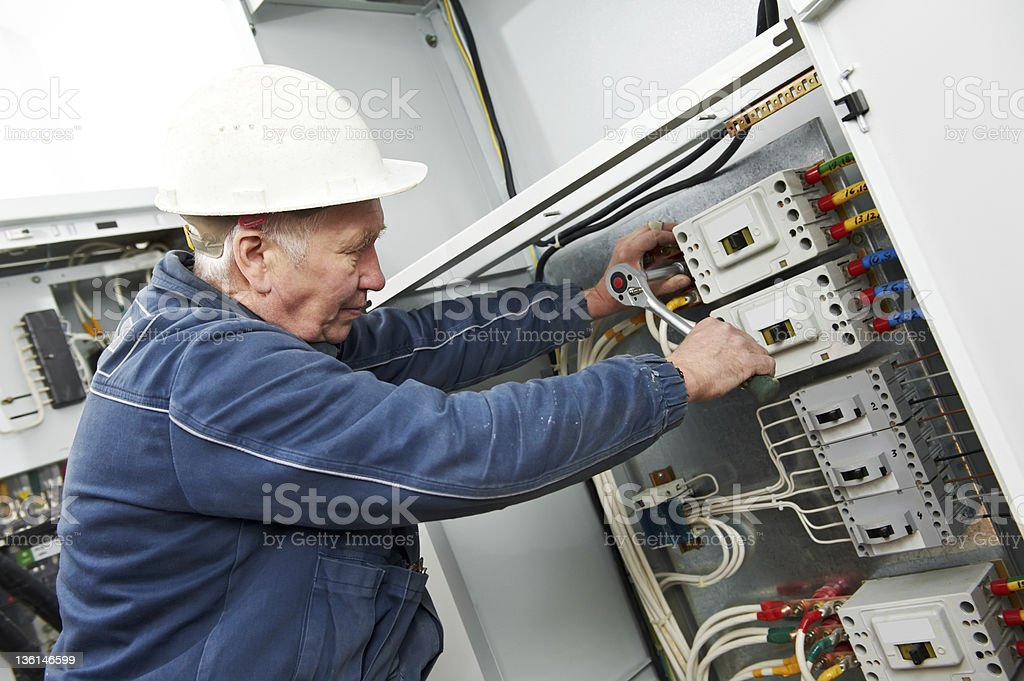 Electrician tighten the screws with spanner royalty-free stock photo
