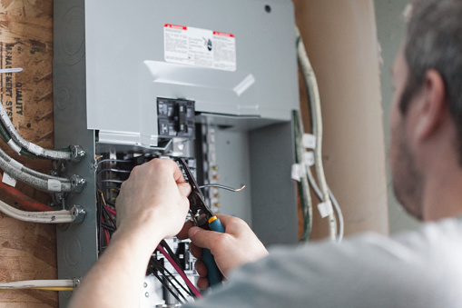 Electrician replacing the distribution board to upgrade a homes electrical panel.