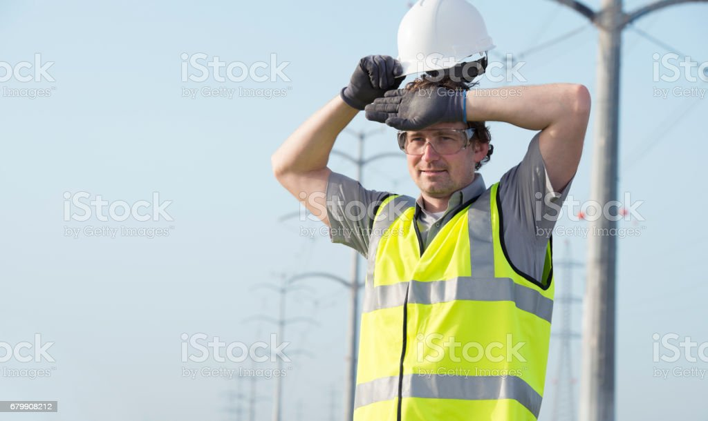 Electrician wipes his forehead. stock photo