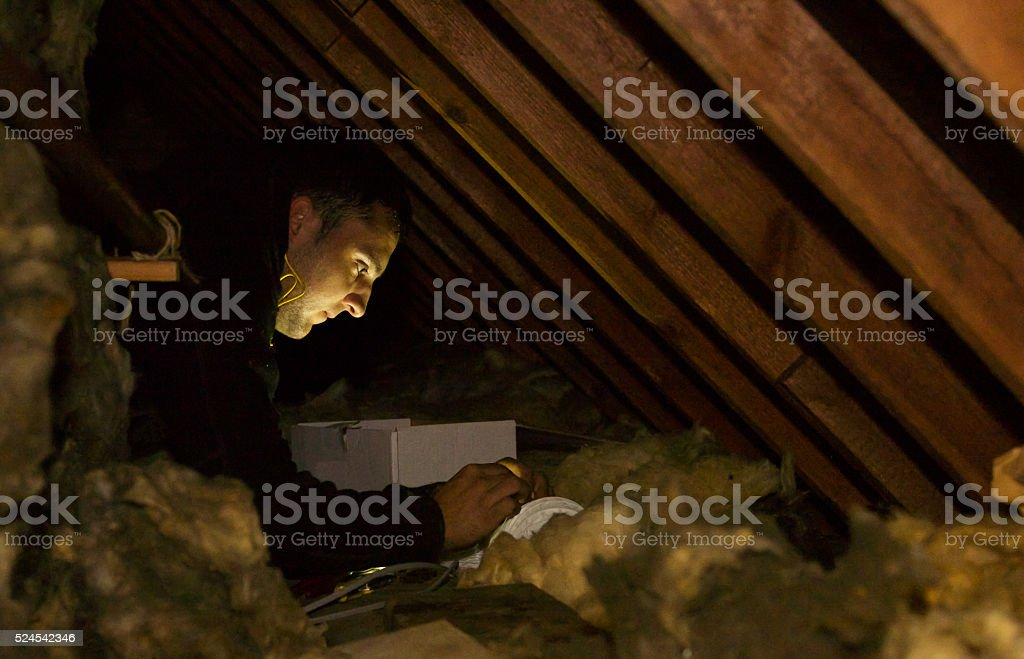 Electrician wiring a new fan extractor in a confined space stock photo