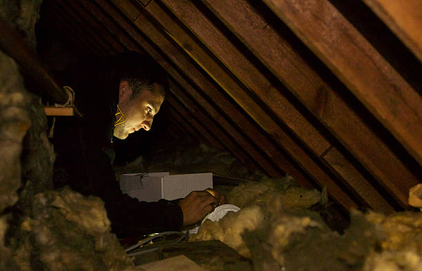 Electrician wiring a new fan extractor in a confined space Electrician wiring a new fan extractor in a confined space - in a residential loft confined space stock pictures, royalty-free photos & images