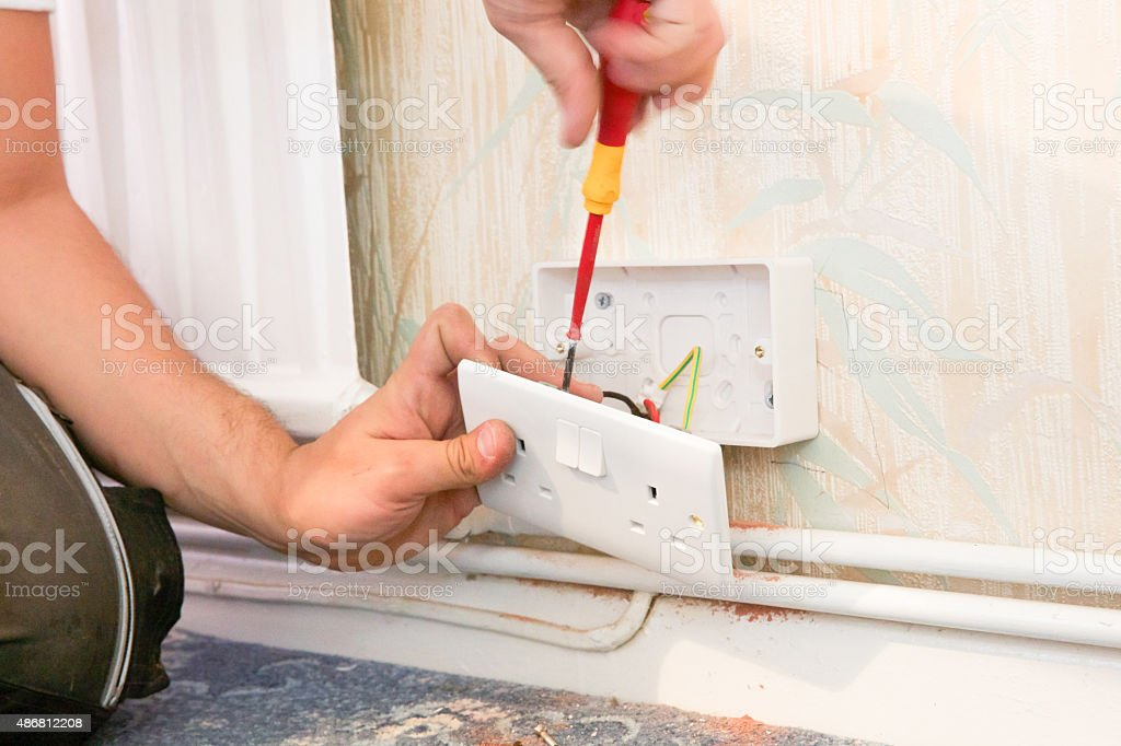 Electrician wiring a new power socket in a residential property. stock photo