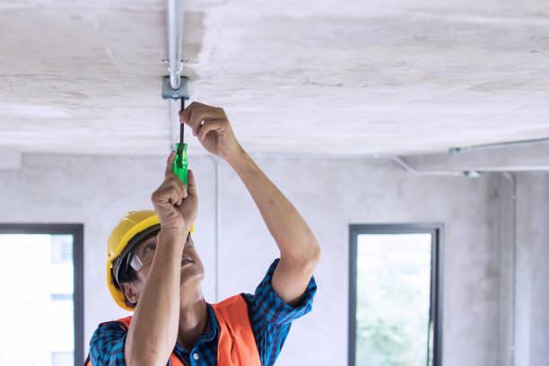 electrician wiring on ceiling in construction site - cavo componente elettrico foto e immagini stock