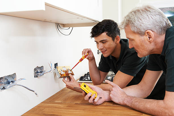 electricista con aprendiz trabajando en nuevo hogar - electricista fotografías e imágenes de stock