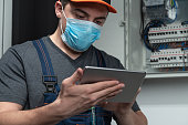 Electrician with n95 face mask hold digital tablet in front fuse box. Photo is taken in studio environment with Sony A7III camera
