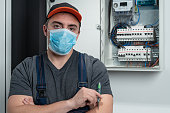 Electrician with N95 protective mask  looking at camera in front fuse box. Photo is taken in studio environment with Sony A7III camera