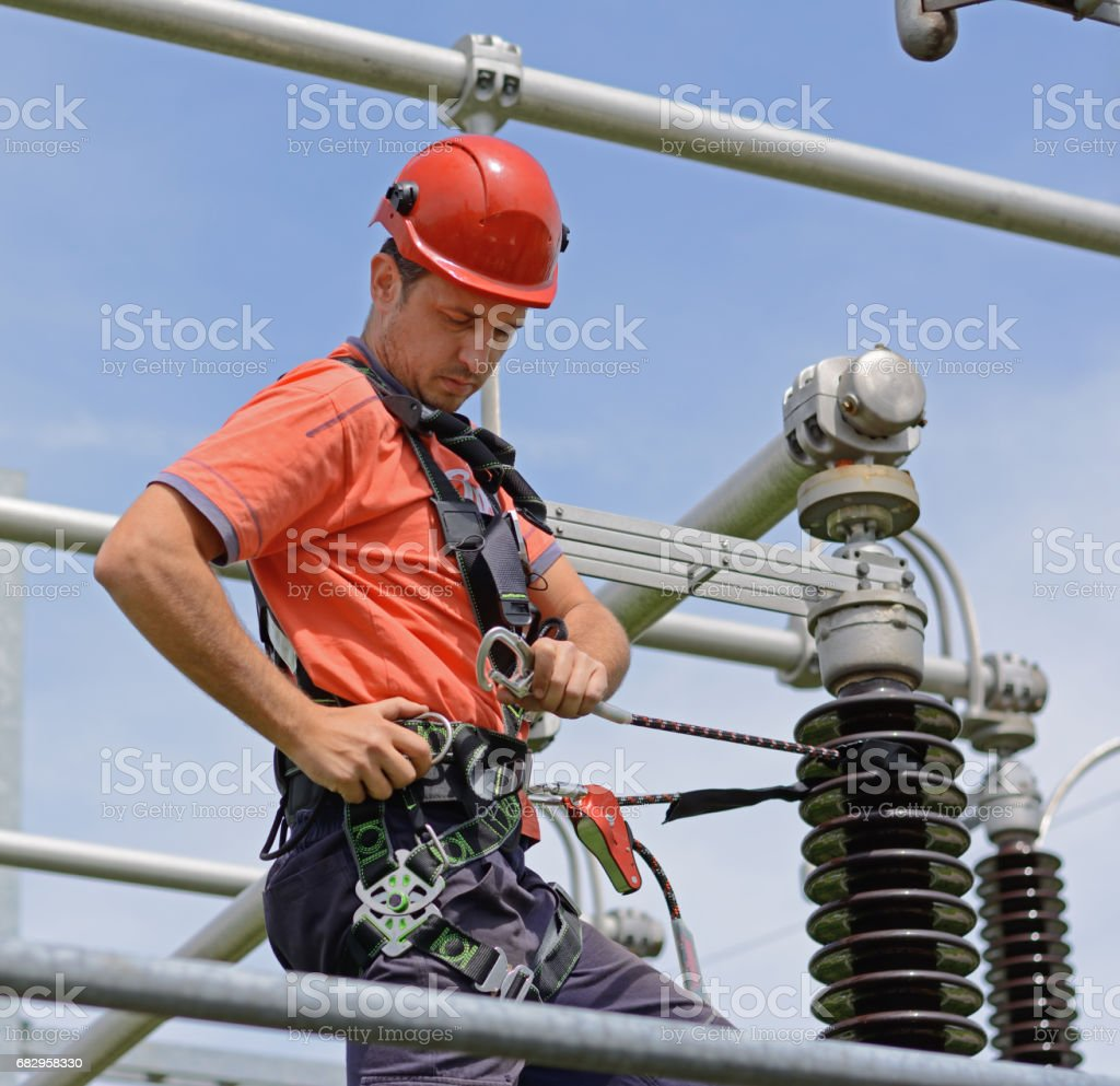 Electrician with protective workwear, hardhat and safety harness working stock photo