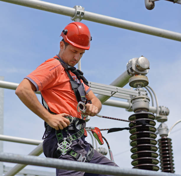 Electrician with protective workwear, hardhat and safety harness working Electricity pylon, manual worker climbing to repair transmission line. Work at height with wrench. safety harness stock pictures, royalty-free photos & images