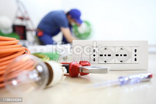 istock electrician work with electrical equipment in the foreground, bulb, tools and socket, electric circuits, electrical wiring 1159434054