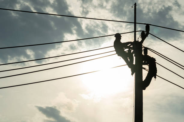 Electrician worker climbing electric power pole to repair the damaged power cable line problems after the storm. Power line support,Technology maintenance and development industry concept stock photo