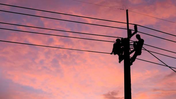 elektryk wspina się na słup energetyczny, aby naprawić uszkodzone problemy z linią kablową po burzy. obsługa linii energetycznych, konserwacja technologii i koncepcja branży rozwoju - przewód składnik elektryczny zdjęcia i obrazy z banku zdjęć