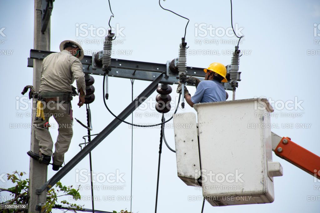 Electrician worker of Metropolitan Electricity Authority working repair electrical system on electricity pillar or Utility pole stock photo
