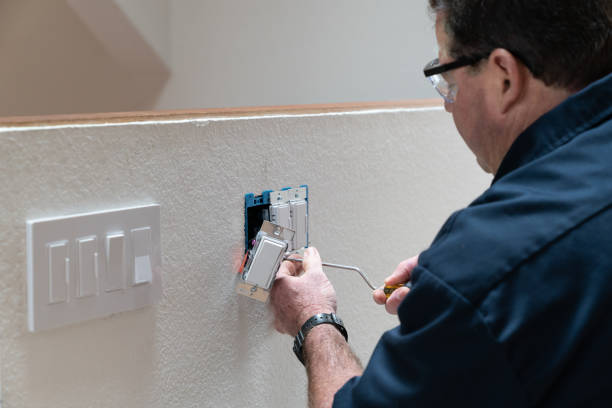 Electrician working in home installing dimmer switched in wall stock photo