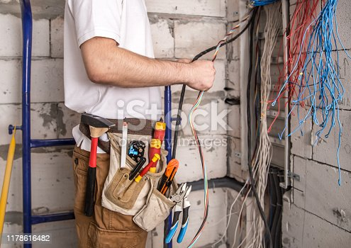 Electrician working near the Board with wires. Installation and connection of electrics. Professional with tools in hand.
