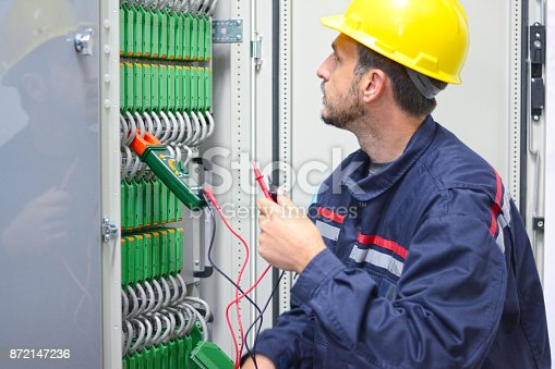 istock Electrician working on a circuit board in electric room. 872147236