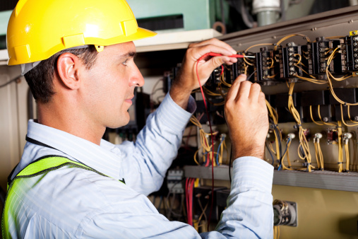 male professional electrician testing industrial machine