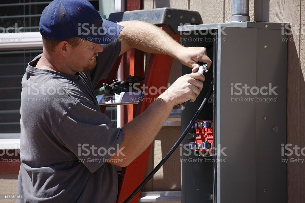 Electrician Working on Electrical Service Panel royalty-free stock photo
