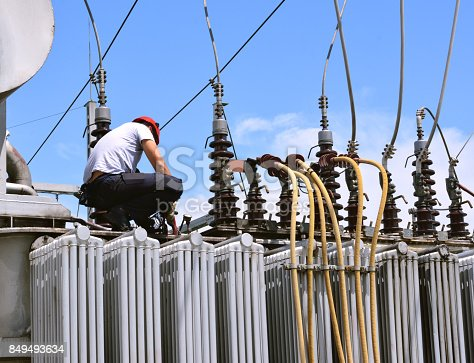 Manual worker in protective workwear and hard hat repairing electricity equipment in power plant