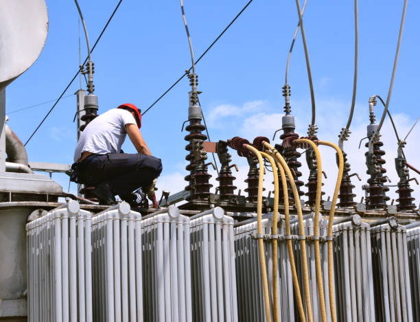 elektryk pracujący nad transformatorem wysokiego napięcia w elektrowni - przewód składnik elektryczny zdjęcia i obrazy z banku zdjęć