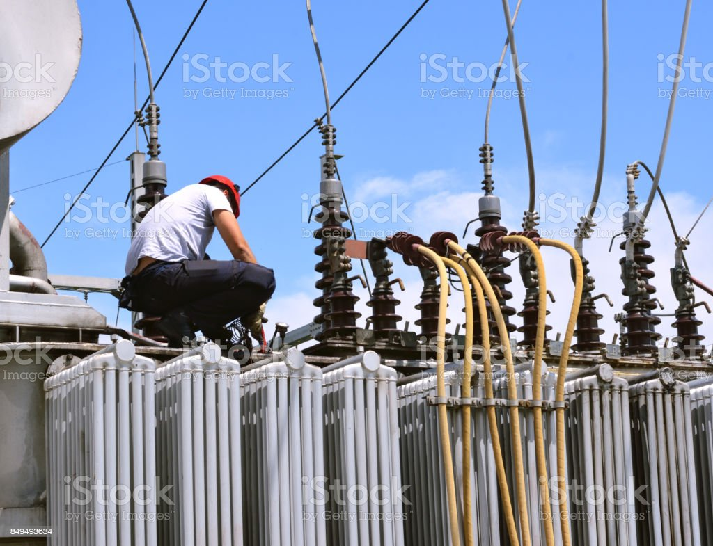 Electrician working on high voltage transformer in power station stock photo