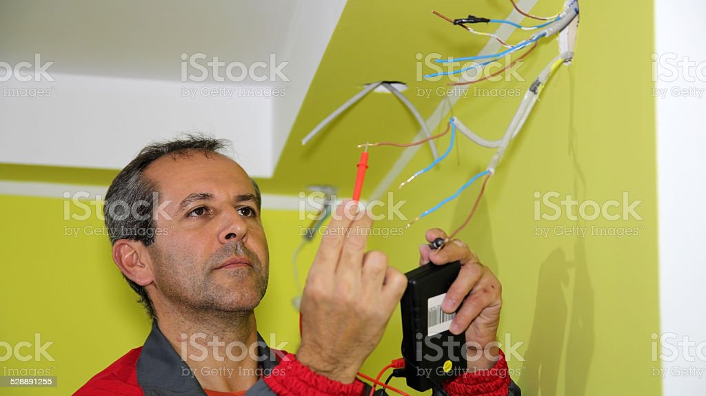 Electrician Working With Measuring Instrument and Wires stock photo