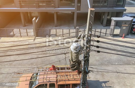 istock Electricians are climbing on electric poles 1148325302